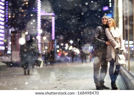Love man and woman embracing outdoors winter snowfall - stock photo