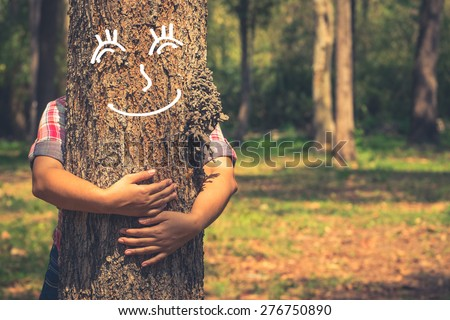 Love nature concept, woman give a hug behind tree trunk with drawing of tree's smile face - stock photo