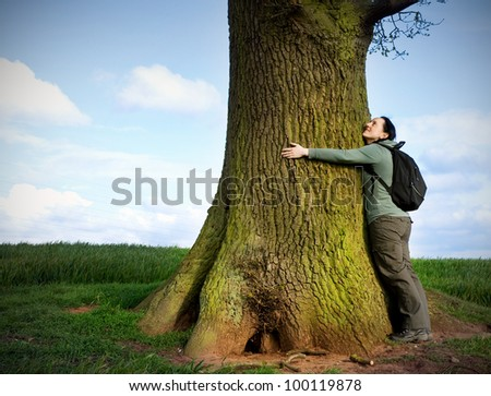 love nature, woman hugging huge tree trunk - stock photo