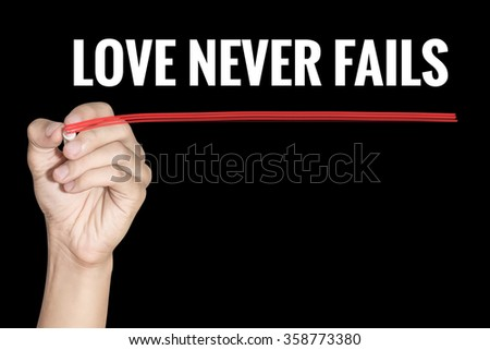 Love Never Fails word writing by men hand holding red highlighter pen on dark background - stock photo