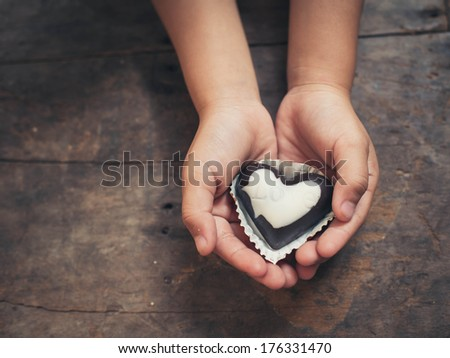 Love note on black and white chocolate in kid's hand - stock photo