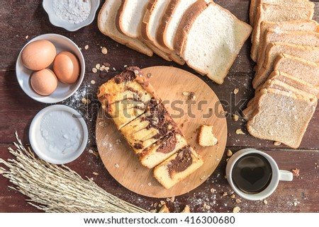 Love of Coffee cup and chocolate marble cake on cutting board with bread and ingredient in kitchen - stock photo