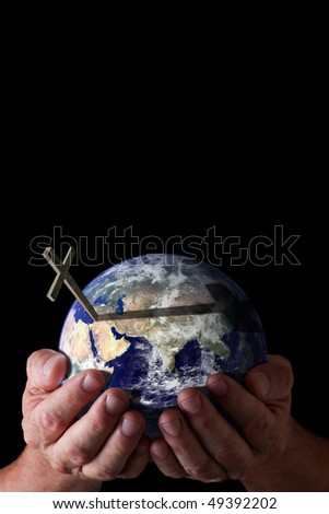 Love of God for world concept.  God's hands holding world with cross on isolated black background. Earth image courtesy of NASA. - stock photo