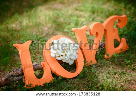 LOVE orange letters with white wedding flowers on grass - stock photo