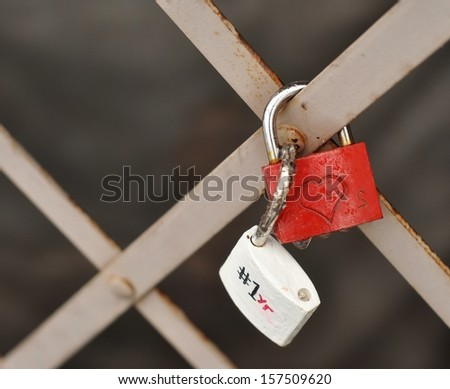 Love padlock tied to a fence. Heart shape. Red and white. - stock photo