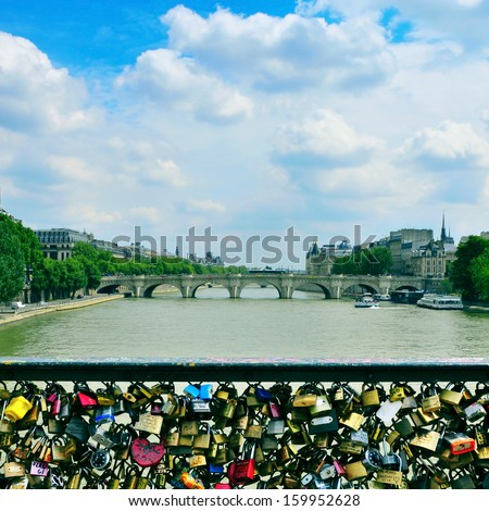 Love padlocks in the Pont des Arts bridge and the Seine River facing the Pont Neuf in Paris, France - stock photo