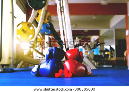 love Pair of Red and Blue boxing gloves hanging on a Blue wall fitness center - stock photo