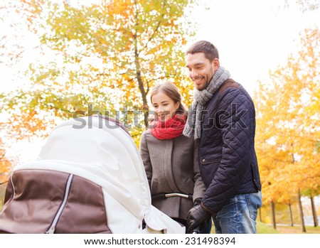 love, parenthood, family, season and people concept - smiling couple with baby pram in autumn park - stock photo