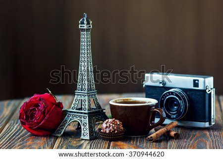 Love Paris! Rose, vintage camera, Eiffel tower, coffee cup, chocolate and cinnamon sticks on wooden background. St Valentine's Day concept. Nostalgic holidays background - stock photo
