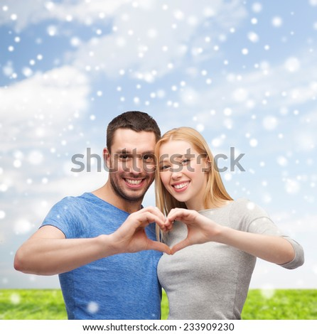 love, people and family concept - smiling couple making heart shape gesture hugging over blue sky, snow and grass background - stock photo