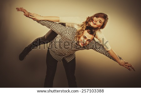 Love people and happiness concept. Smiling young couple having fun, man giving piggyback ride to woman - stock photo