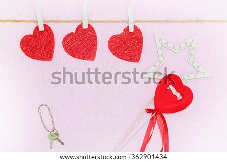 Love red hearts hanging on white clothespins over pink background. Keys on chain and a star at the bottom of the postcard - stock photo
