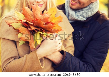 love, relationship, family and people concept - close up of smiling couple with bunch of leaves hugging in autumn park - stock photo