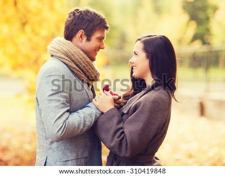 love, relationship, family and people concept - close up of smiling couple with red gift box in autumn park - stock photo