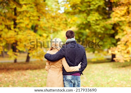 love, relationship, family and people concept - couple hugging in autumn park from back - stock photo