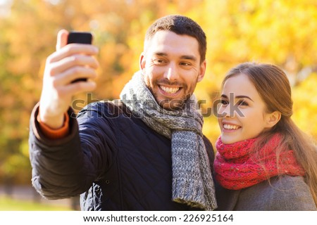love, relationship, family and people concept - smiling couple hugging and taking selfie with smartphone in autumn park - stock photo