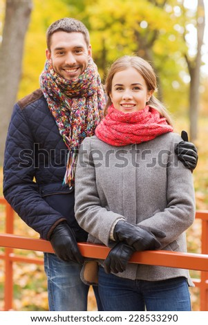 love, relationship, family, season and people concept - smiling couple hugging on bridge in autumn park