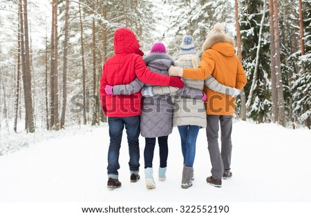 love, relationship, season, friendship and people concept - group of happy men and women walking in winter forest - stock photo