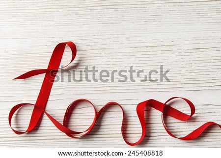 Love Ribbon Word Twisted over White Wooden Background. Valentine Day Concept. - stock photo