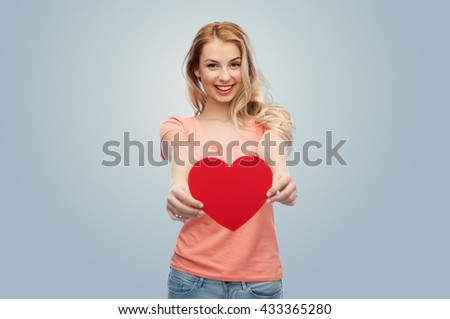 love, romance, charity, valentines day and people concept - smiling young woman or teenage girl with blank red heart shape over gray background