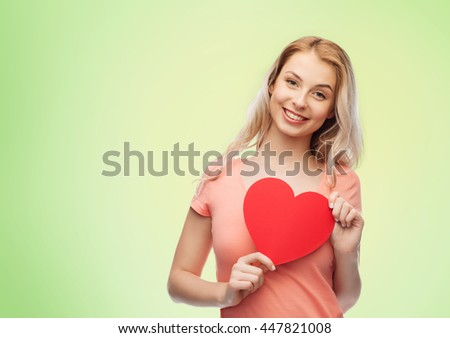 love, romance, charity, valentines day and people concept - smiling young woman or teenage girl with blank red heart shape over green natural background