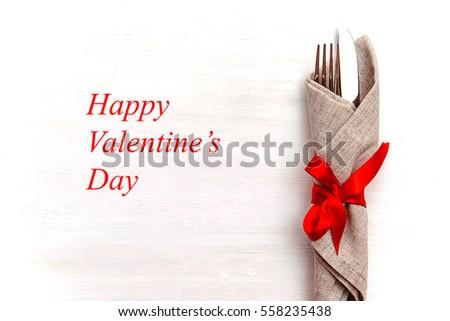 Tình yêu, lãng mạn khái niệm - Thiết lập bảng lễ hội cho Ngày Valentine với nĩa và dao trên nền gỗ màu trắng.
