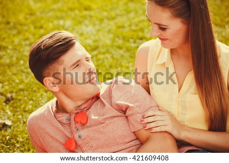 Love romance relationship dating relax concept. Affectionate couple on grass. Young enamoured girl and boy show affection in park.  - stock photo