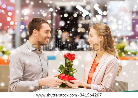 love, romance, valentines day, couple and people concept - happy young man with red flowers giving present to smiling woman at cafe in mall with snow effect