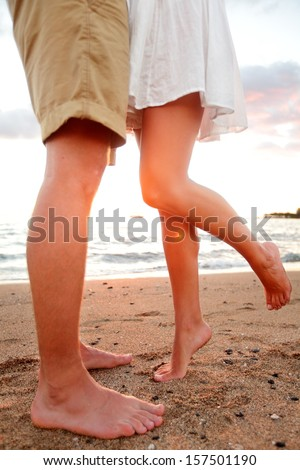 Love - romantic couple dating on beach kissing and embracing. Happiness and romance travel concept with happy young couple barefoot in sand enjoying beautiful sunset. - stock photo