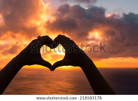 Love shape hand silhouette against sunset - stock photo