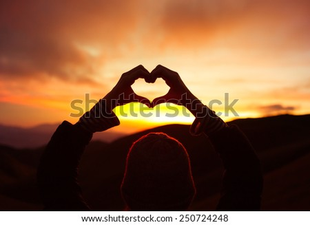 Love shape hand silhouette in the sky - stock photo