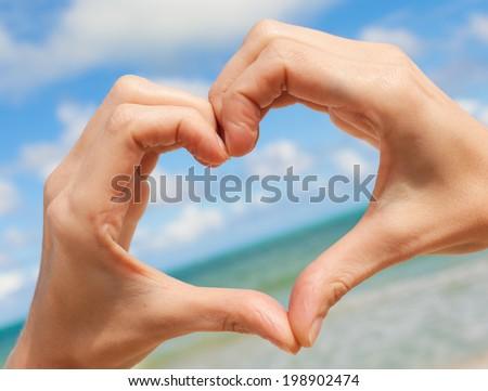 Love shape hands against the sky. - stock photo