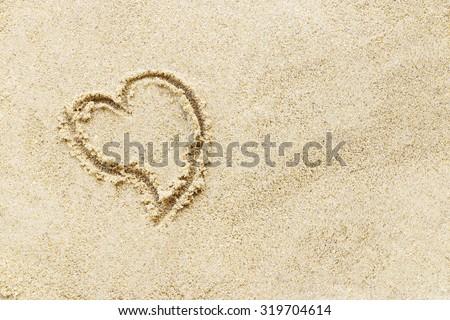 Love sign writing on sand beach. - stock photo