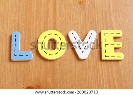 LOVE, spell by woody puzzle letters with woody background - stock photo