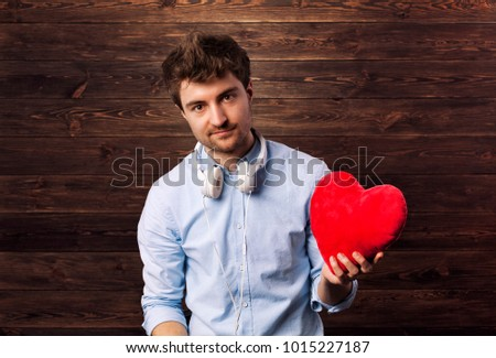 Love story and Valentines Day concept with young handsome man holding a read heart.