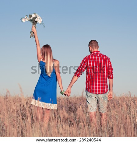Love story. Beautiful young couple walking in meadow, outdoor. Portrait of stylish fashion man and woman posing in summer in field. Series. Back view - stock photo