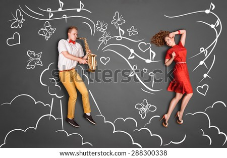 Love story concept of a romantic couple against chalk drawings heaven background. Male playing the sax for his girlfriend. - stock photo