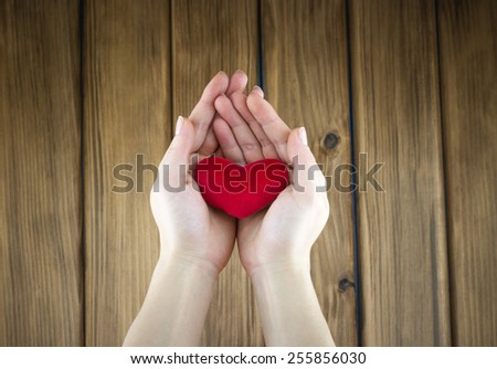 Love story concept. Top view of female hands holding red heart shape on wooden background - stock photo