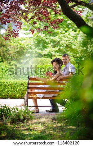 Love story of happy couple. Groom and Bride sitting on a bench in a park. wedding dress. Bridal wedding bouquet of flowers. feelings, relations, passion