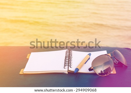 love summer decorate with eyeglasses and note book on wooden floor on the blue sea,vintage color tone. - stock photo