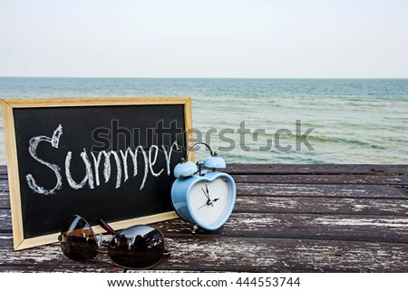love summer time decorate with eyeglasses and chalkboard on wooden floor over blue sea  background ,summer holiday travel and shopping concept. - stock photo