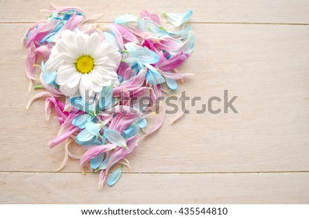 Love symbol on wooden background maid by blue and pink petals with daisy flower. - stock photo
