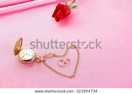Love takes time - golden pocket watch, rings, red rose on pink background. - stock photo