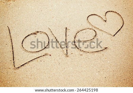 Love text and heart drawn on sand  - stock photo