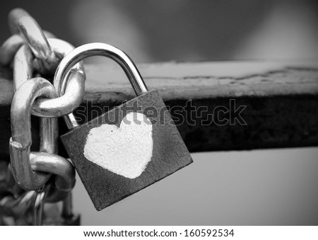 Love that cannot be broken, shown through a heart padlock chained to a fence, black and white.