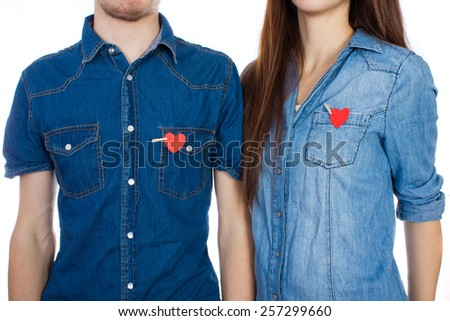 Love the girl and the guy. Smiling couple standing isolated on white background with a heart in pocket. A woman and a man in a denim shirt with red paper hearts in his pocket a small clothespin - stock photo