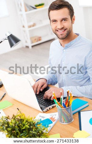 Love the job you do. Handsome young man in shirt working on laptop and smiling at camera while sitting at his working place - stock photo