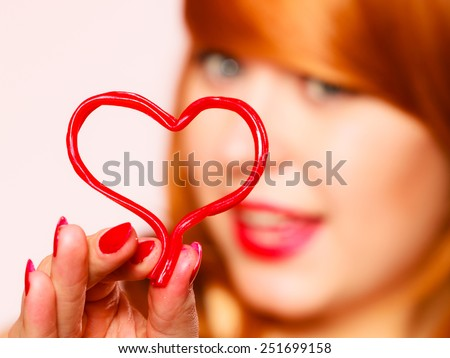 Love to candy and sweets. Valentine's Day concept. Gorgeous young red haired woman holding candy heart on pink background in studio.
