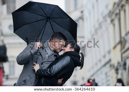 love together in the street weekend walking in the street kissing umbrella rain