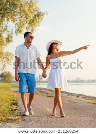 love, travel, tourism, gesture and people concept - smiling couple on summer vacation wearing sunglasses and pointing finger walking at seaside